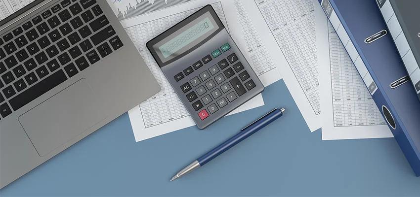 Aktenordner, Kalkulationen Taschenrechner und Laptop auf Schreibtisch